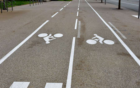 Bike lanes or cycle paths in opposite directions along the car road in the city of Belfort in France. The biking symbols and the lines are painted in white color. Reklamní fotografie