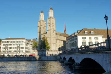 Quay Bridge in Zurich in lateral view with Grossmunster cathedral on the Limmat River bank on the background surrounded by historical buildings enlighten by sun.