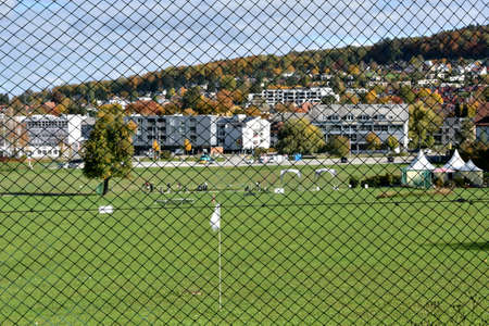 Golf club in Urdorf on a sunny autumn Saturday afternoon from behind a fence with village center in the background. Stock Photo