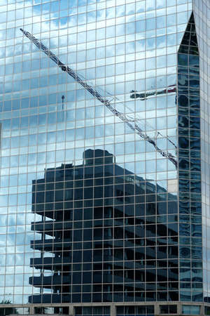 Rotterdam / Netherlands - 06 18 2020: A facade of a modern corporate building reflecting another building in construction together with construction machinery and sky with clouds.