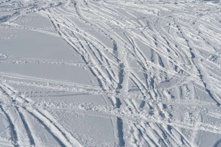 Ski slope or ski piste illuminated by direct sun covered by irregular traces of skis or trajectories in crisp white snow in Swiss Alps, Hoch Ybrig in Switzerland.