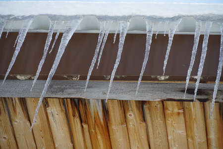 Melting icicles hanging from a roof covered with a layer of snow. There are drops of water falling down from them. Slight thaw in the afternoon sun.