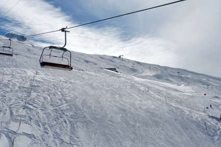Empty chair lifts in ski resort Switzerland closing up because of pandemic. The last skiers are on the slope.