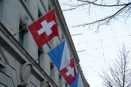 Detail of a Swiss federal flag and flag of canton Zurich displayed on the facade of a historic building in the city center of Zurich. Low angle view.