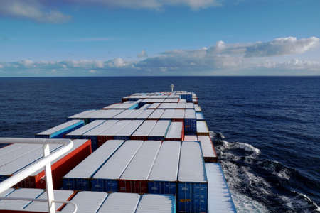 Container vessel covered with snow on top of the container sailing over the Pacific ocean during winter season.