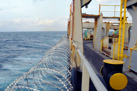 Barbed wire or razor wire attached to the ship hull, superstructure and railings to protect the crew against piracy attack passing Gulf of Guinea in West Africa.
