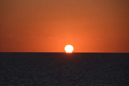 View from merchant ship on sunset in Atlantic ocean with copy space. The sky is displayed in varies harmonic shades of red, orange and yellow colours during calm weather in spring time.