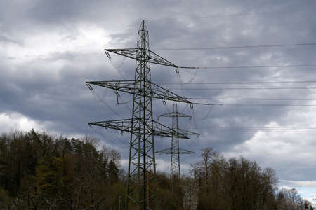 High voltage pylons for transfer of electricity in woodland of dicdeous trees in early spring, in village Birmensdorf. There is a dramatic cloudy sky on the background and a lot of copy space.