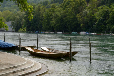 Wooden boats moored at promenade along Rhine river in Schaffhausen, Switzerland. They are called weidling boot in German language and they are traditional Swiss boats. River bank is regulated.