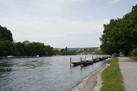 Promenade along Rhine river in Schaffhausen, Switzerland. There are wooden boats moored along the river bank. They are called weidling boot in German language and they are traditional Swiss boats.