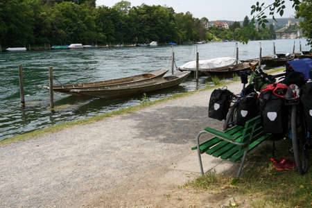 Wooden boats called weidling in German language. Boats are moored at wooden mooring poles on Rhine river in city Schaffhausen in Switzerland. On river bank there are bicycles leaned on wooden bench. Banque d'images