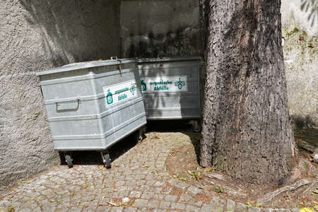 Two metal containers placed in a corner of a yard surrounded with high bricked fence. On them here is inscription in German language saying organic waste. In the foreground there is a tree trunk.