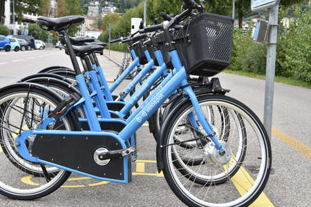 Locarno, Switzerland 09 26 2020: Bike sharing system in cities and towns by company Velospot. Blue E-bikes can be borrowed only at a Velospot station and are activated by card or mobile phone.