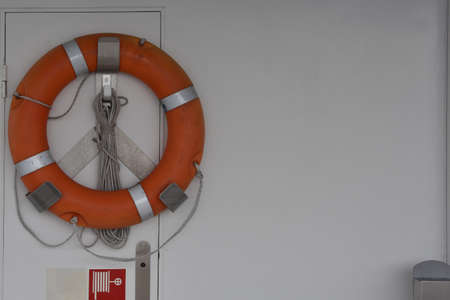 Orange life buoy on the white wall of tourist cruiser vessel with copy space.