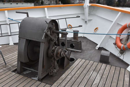 Anchor gear fixed in bow of a tourist cruiser ship painted white. On main weather bottom deck is also installed double bollards and wooden boarder floor.