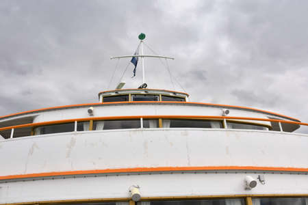 Wheelhouse with clear view screen of cruise tourist vessel painted white with yellow rims. View from forecastle main deck on the bridge with mast, blue flag and radar during winter overcast weather.