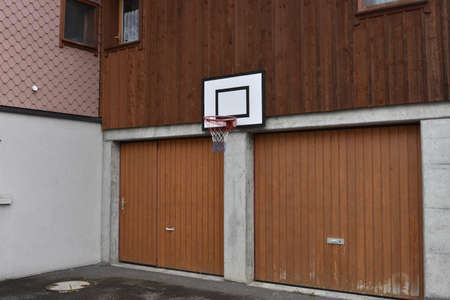 Basketball board and hoop net fixed on the wall of family house over two garages. Banque d'images