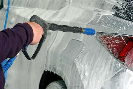 Man washing a car with high pressure washer or cleaner. The car is covered with foam.