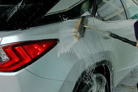 Man washing a car with a brush spreading shampoo over it. A scene from self service car wash. Banque d'images
