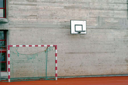 Cement wall with a basketball hoop and handball goal on the ground beside it. Banque d'images
