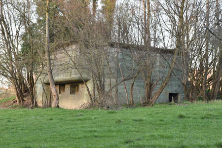 Old concrete bunker or fallout shelter among tress that was made to prepare Switzerland for war or to protect the Swiss people from potential onset of war and nuclear devastation. Éditoriale