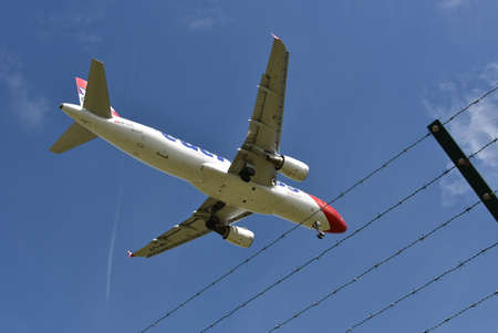 Close up view on the airplane in the blue sky crossing the fence of the airport during landing. Éditoriale
