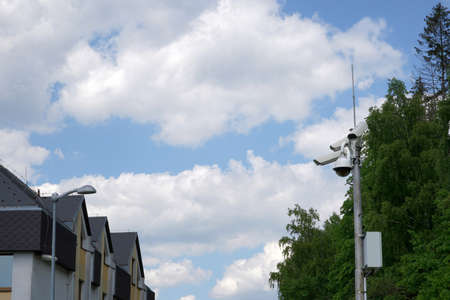 Cctv camera attached on a metal pole installed in a residential quarter for security and safety. There is sky on the background and a lot of copy space.