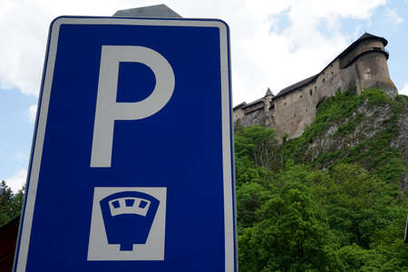 Traffic sign for paid parking in tourist area around Orava castle in Slovakia. Low angle view with the silhouette of the castle on the background. Banque d'images
