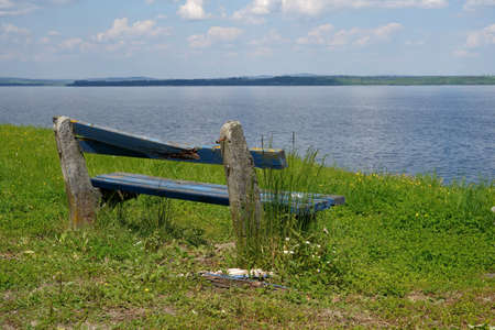 Broken bench on the coast Orava water reservoir in Slovakia.  View on the water and the horizon bordered with trees.