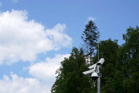 Cctv camera attached on a metal pole with coniferous trees and sky on the background and a lot of copy space. It serves for protection of property for both private persons and copamanies. Banque d'images