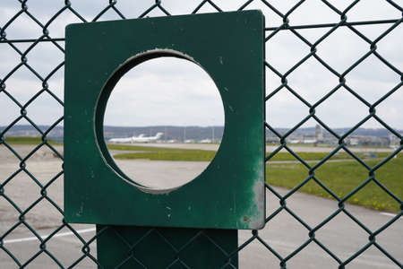 Observation hole in the fence around an airport. There are outlines of the landed airplanes in the background.