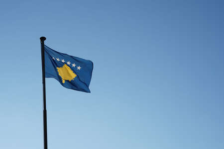 Kosovo flag hoisted on a flagpole waving in the wind. Low angle view against blue sky with plenty of copy space. Banque d'images