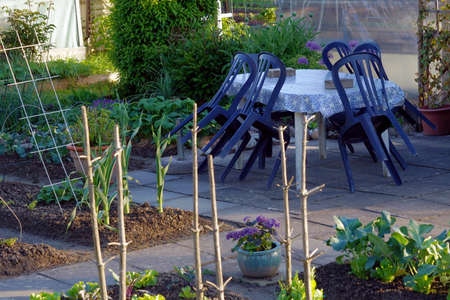 Hobby garden with a paved seating place. There is a table with plastic chairs among vegetable patches. Banque d'images