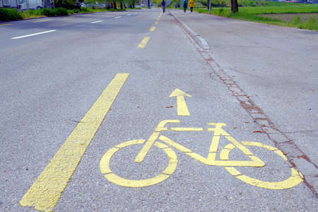 Bicycle lane with yellow marking on the ground in Switzerland. On the right, there is sidewalk for pedestrians. In the background are silhouettes of pedestrians and one person on bike. Banque d'images