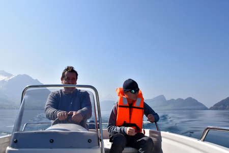 Father and son making a tripp on motorboat on lake Lucerne in Switzerland. Boy is wearing orange life jacket and sun glasses. Man is at steering wheel. On background there are snow-capped Swiss Alps. Banque d'images