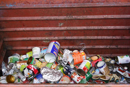 Aluminium cans and other objects in a large metal container with copy space. Separated house waste. Banque d'images