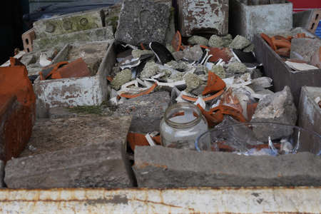 Debris from construction or building site. There are pieces of concrete, bricks, roofing tiles and glass. Close up view on the content of a large industrial debris container.