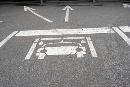 Pictogram of a car on the ground with two arrows showing direction to car wash facility. Close up view. The arrows show to the boxes for self service.