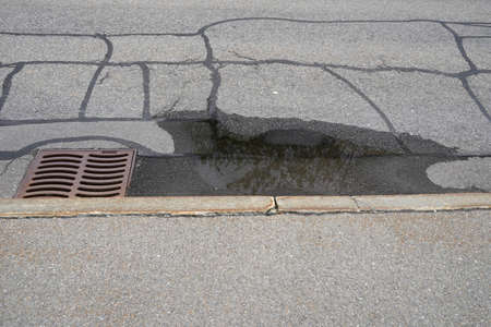 Road with a gully. There is a puddle of rain water because it is uneven. On the road there are traces of repairs.