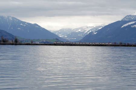 Lake Zurich in winter. A train is passing on a bridge across the lake. Alp mountains covered with snow are on the background.