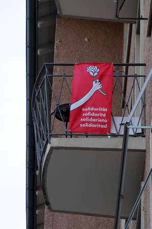Red banner with word solidarity in German, French, Italian and Spanish. Above the words there is a hand holding a rose. The banner is attached on railings of a balcony. Low angle view. Banque d'images