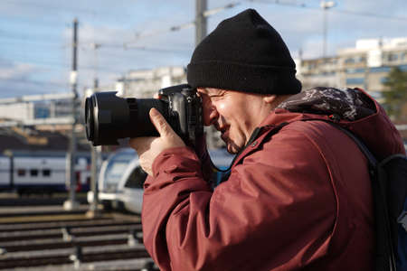 A man taking photos of trains in winter. Side view photo. He is wearing a cap and winter jacket.