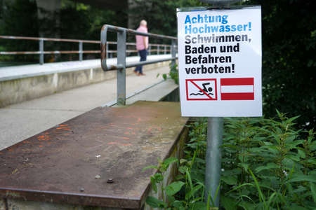 Signpost on bridge over river Limmat in Switzerland. It is in German language and it says beware of high water. Bathing, swimming and trespassing is forbidden. In background there is a silhouette.