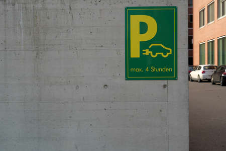 Sign showing parking place with charging stations for electric cars in green and yellow. It is installed on a wall. In background are parked cars. There is text in German parking maximum 4 hours.