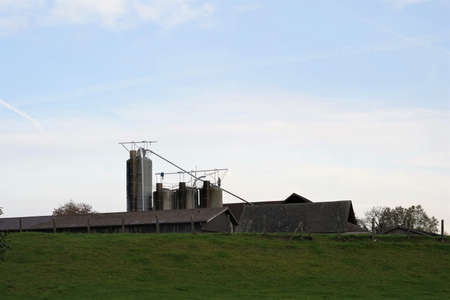Dairy farm in Switzerland. There are buildings and silos. The farm is on a hill covered with fresh green grass. There is pastel sky on the background with a lot of copy space.