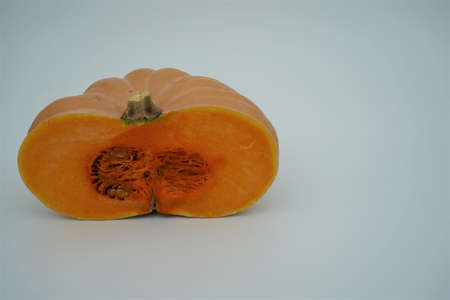 Half of a butternut squash or pumpkin isolated with a lot of copy space. Seasonal vegetable in bright orange color contrasting with the background. Banque d'images