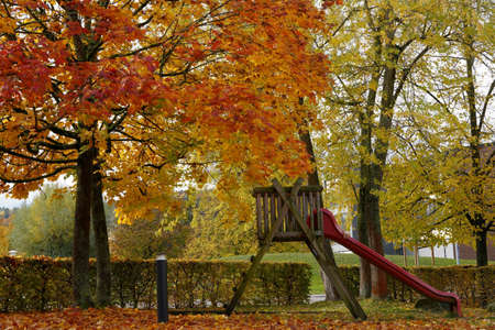 Autumn scene in a park. There are trees with colorful foliage, low hedge and slide for children. Dry leaves are on the ground as well. A tranquil seasonal background scene with copy space. Banque d'images