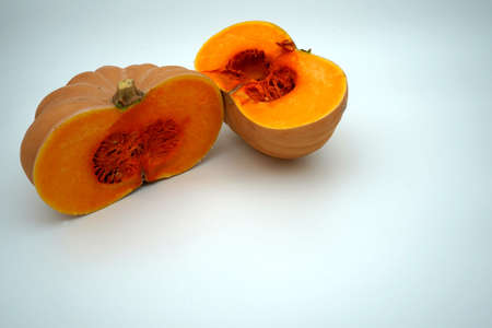 A butternut squash or pumpkin cut into two halves isolated with a lot of copy space. Seasonal vegetable in bright orange color contrasting with the background.