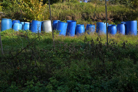 Plastic barrels for fermentation of fruits. They are arranged in row in garden in autumn. The barrels are in different shades of blue color. There is copy space in the foreground. Banque d'images