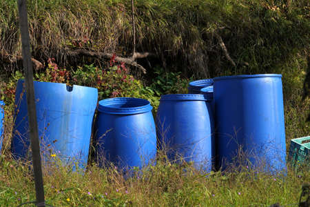 Plastic barrels for fermentation of fruits. They are arranged in a group in the garden in autumn. The barrels are in blue color. There is copy space in the foreground. Banque d'images